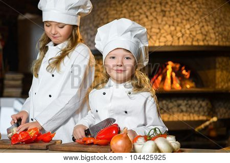 Funny happy chef girls cooking at restaurant kitchen