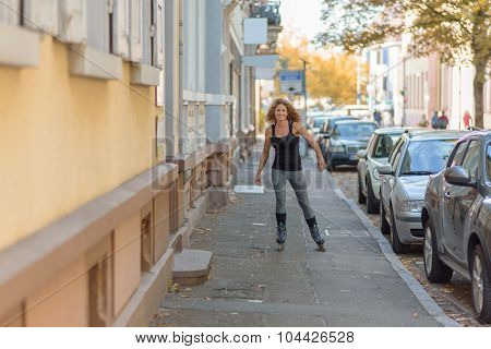 Young Woman Roller Skating Down An Urban Street