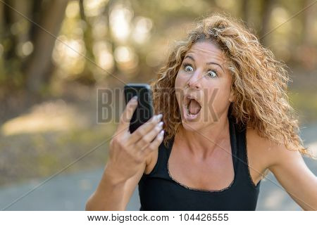 Young Woman Reacting In Horror To A Text Message