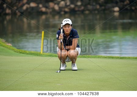 KUALA LUMPUR, MALAYSIA - OCTOBER 10, 2015: China's Xi Yu Lin checks the green of the 18th hole of the KL Golf & Country Club during the 2015 Sime Darby LPGA Malaysia golf tournament.