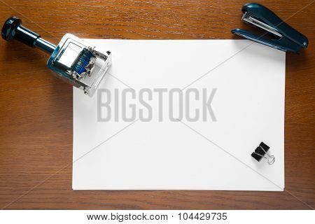 Stamp And A Blank Sheet Of Paper On An Office Desk Close Up