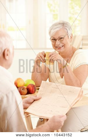 Smiling Elderly Wife Sitting At Table With Mug