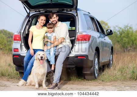 Cheerful married couple and child with puppy near transport