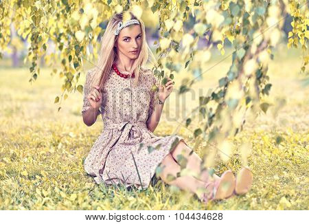 Beautiful playful woman sitting under birch tree, outdoors