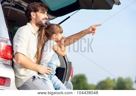 Cute man with child are resting in nature near transport