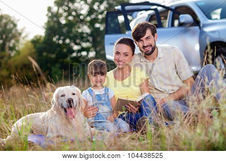 Cheerful parents and child with pet in trip