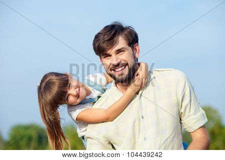 Pretty male parent and child are playing in meadow