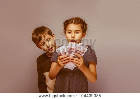 girl holding money bills in the hands of the boy opened his mout
