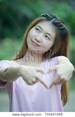 Asia Happy Young Woman Making Heart Sign With Hands