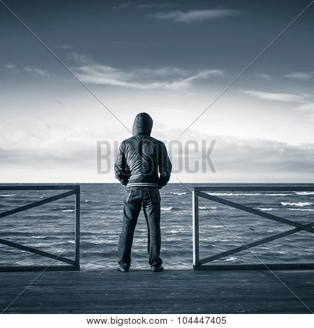Young Man Looking On The Sea From Wooden Pier