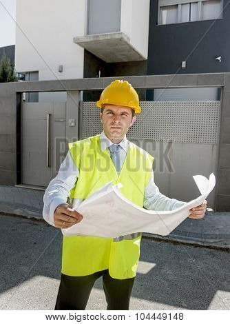 Young Attractive Foreman Worker Supervising Building Blueprints Outdoors Wearing Construction Helmet