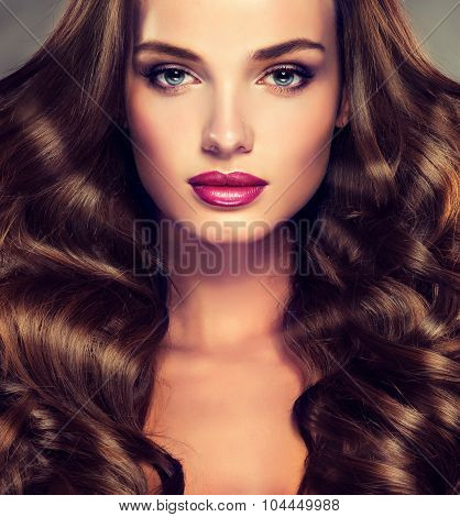 Girl model with long curly  brunette  hair . Trendy image of a brown head woman .