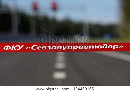 NOVOPRIOZERSK HIGHWAY, LENINGRAD OBLAST, RUSSIA - SEPTEMBER 11, 2015: Red ribbon across the road during the opening of new stretch of Novopriozersk highway. Construction began in 2013
