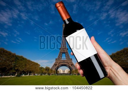 Hand holding a bottle of wine in Paris