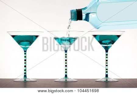 liquor being poured into martini glasses
