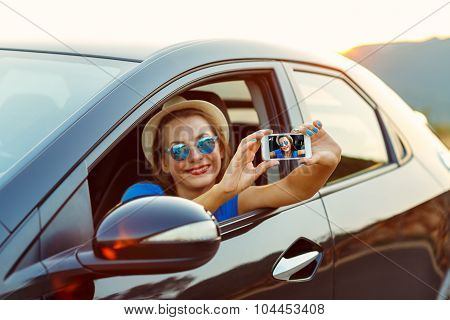 Young Happy Woman In Hat And Sunglasses Making Self Portrait Sitting In The Car
