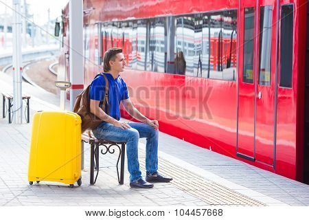 Young man with baggage at a train station near express
