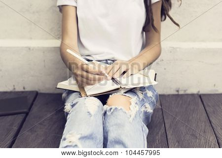 Girl Making Notes In The Diary And Sitting On A Wooden Floor