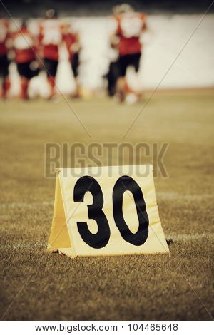 Football yard line with a sign in the foreground - retro styled photo