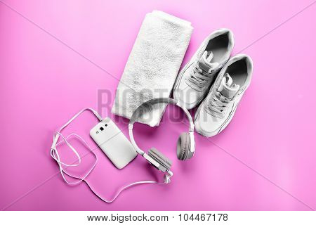 Sport shoes, towel and headphones on pink background