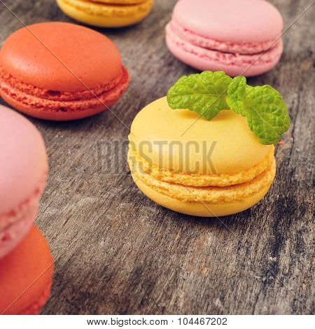 some appetizing macarons with different colors and flavors on a rustic wooden table