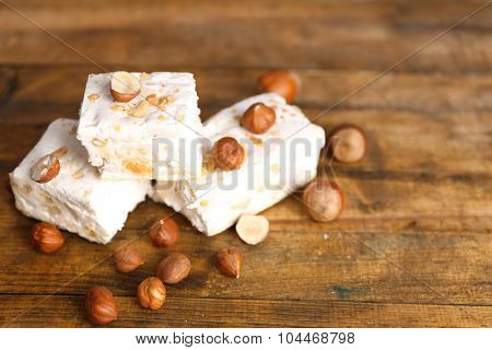 Sweet nougat with hazelnuts on wooden background
