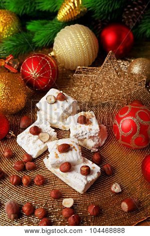 Sweet nougat with hazelnuts and Christmas decoration table close up