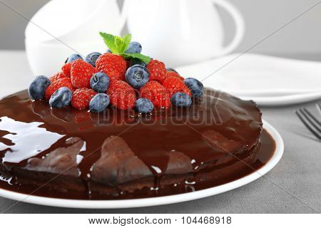 Delicious chocolate cake with summer berries on grey tablecloth background