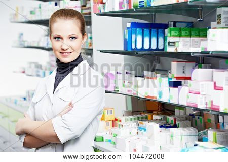 Pharmaceutical industry. Cheerful pharmacist chemist woman standing in pharmacy drugstore