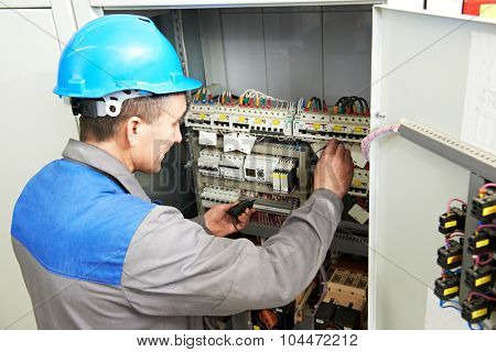 electrician worker with switching on the electric power switch in fuse board