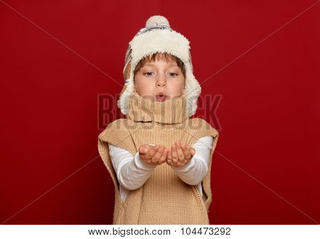 winter, people, xmas concept - girl in hat and sweater blowing on palms on red background