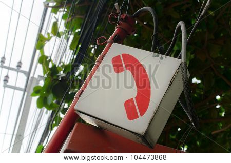 Old telephone sign over telephone booth