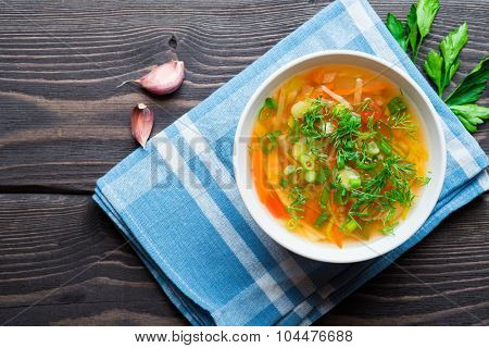 Vegetable soup with carrot, tomatoes, turnip and leek in white bowl on a wooden background