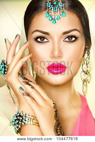 Beautiful fashion Indian woman portrait with oriental accessories- earrings, bracelets and rings. Indian girl with black henna tattoos and beauty jewels. Hindu model with perfect make-up. India