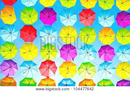 Colorful umbrellas background. Colourful umbrellas urban street decoration. Hanging Multicoloured umbrellas over blue sky. Bright Colors backdrop