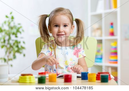 child girl painting with colourful paints