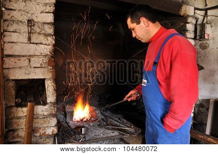 Blacksmith Forges A Red-hot Iron In The Forge