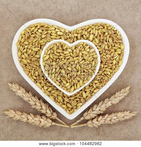 Kamut khorasan wheat grain health food in heart shaped porcelain dishes with sheaths over brown grunge paper background.