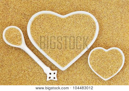 Bulgur wheat super food in heart shaped bowls and porcelain spoon forming an abstract background.
