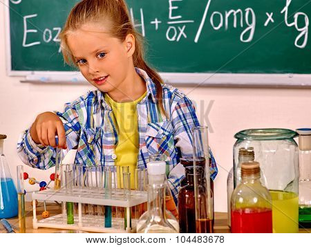 Child holding flask and  do experiments in chemistry class.