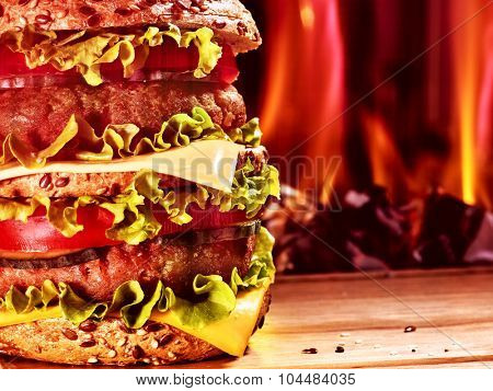Double patty hamburger on wooden board on background of fire. Food still life.