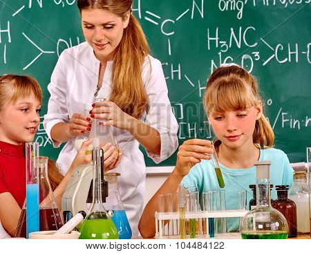 Teacher with two  children girl holding flask in chemistry class.