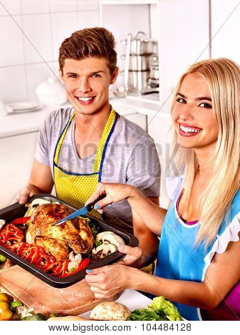Happy couple cooking together chicken at kitchen.