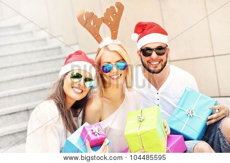 A picture of group of friends in Santa's hats sitting in the city with presents
