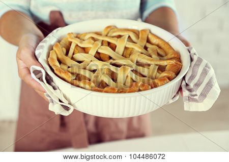 Homemade apple pie  in female hands, on light background