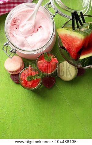 Watermelon ice cream in glass jars  on color wooden background