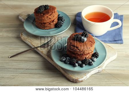 Cakes with berries and tea on the table