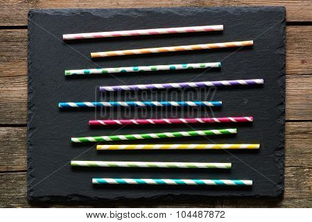 Drinking straws on slate background
