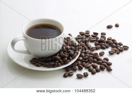 Cup Of Coffee And Coffee Beans On A White