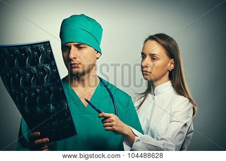 Medical doctors team with MRI spinal scan portrait against grey background
